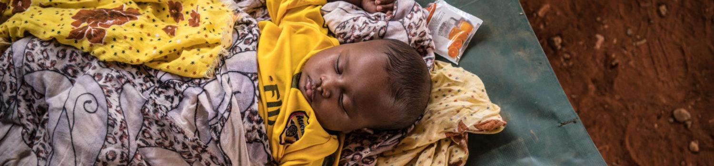 En lille dreng ramt af kolera sover i et behandlingscenter