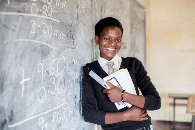 Afrikans teenage pige læner sig op ad tavlen på sin unicef støttede skole