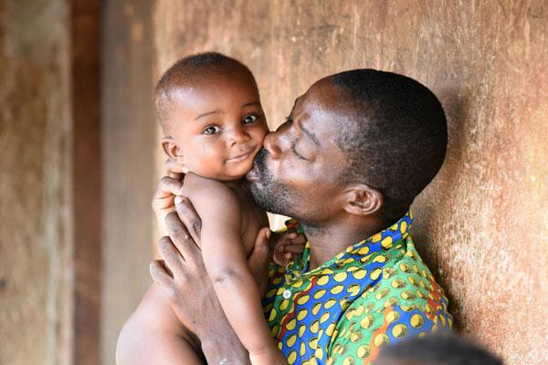 En far kysser sin baby på kinden