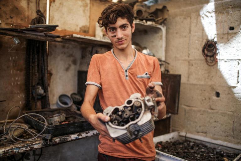 Palestisk teenage dreng arbejder som mekaniker
