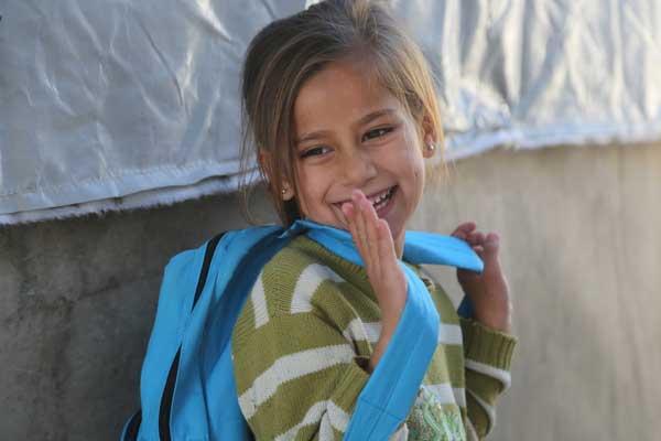 Lille smilende pige med unicef rygsæk på ryggen
